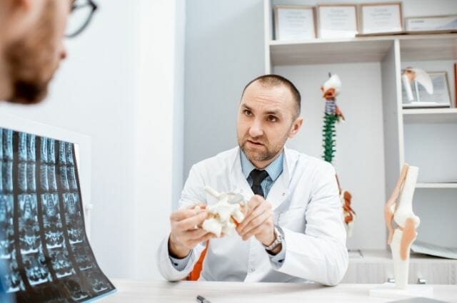 radiologist explaining the spinal condition of a patient